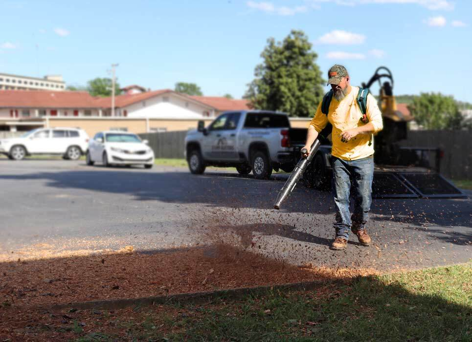 Stump Busters employee blowing wood chips after stump grinding